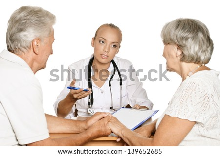 Elderly patients couple came to visit a young doctor - stock photo