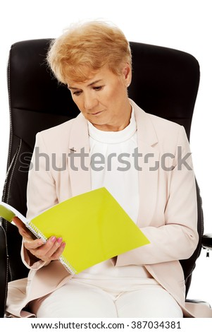 Elderly pensive focused business woman reading notes