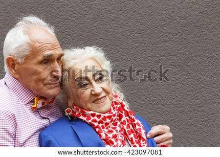 Elderly people . An old man gently covered his wife jacket on a background of gray wall. Concept: Happy old age, care, love. Festive beautiful makeup.