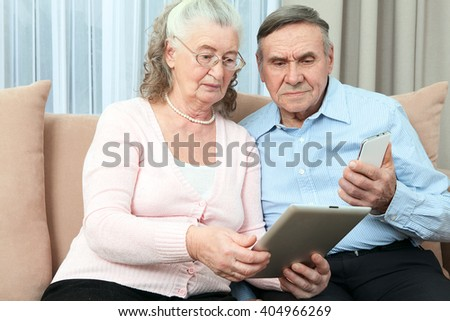 Elderly people. Elderly couple having fun in communicating with the family on the internet in the comfortable living room  - stock photo