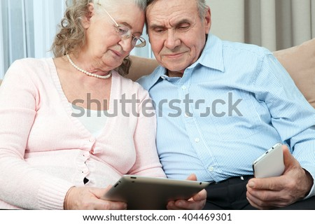 Elderly people. Elderly couple holding laptop, smartphone and make purchases over the Internet in the cozy living room of the house. Elderly people communicate fun. - stock photo