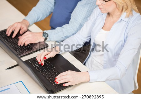 Elderly people sitting at the desk and working on laptops - stock photo