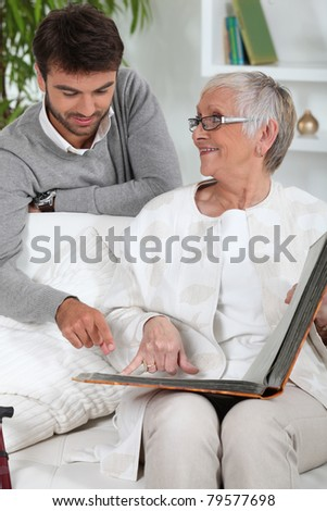 Elderly person looking at photos with son - stock photo