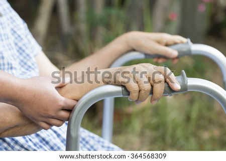 Elderly physical therapy by caregiver in backyard at home - stock photo