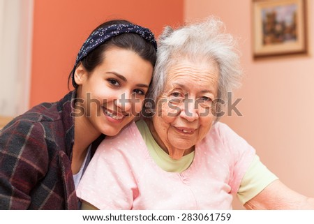 Elderly 80 plus year old grandmother with granddaughter in a home setting. - stock photo
