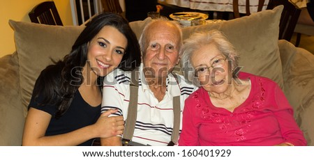 Elderly 80 plus year old grandparents with granddaughter in a home setting. - stock photo