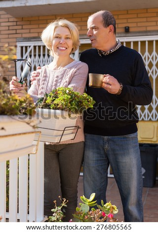Elderly positive woman talking with male neighbor at balcon