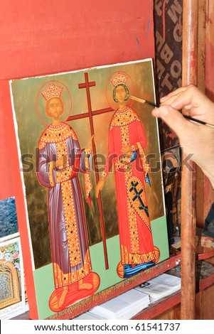 Elderly priest's hand painting an icon in the monastery's studio