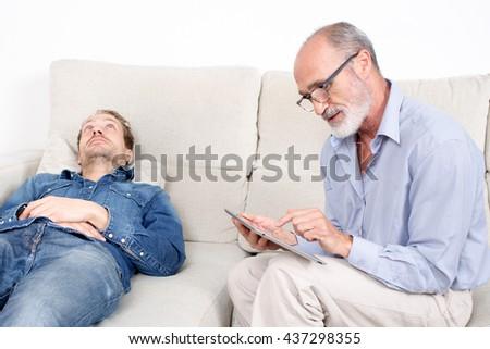 Elderly psychologist listening to a man - stock photo