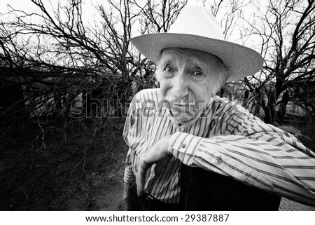 Elderly rancher with sad eyes in a straw hat - stock photo