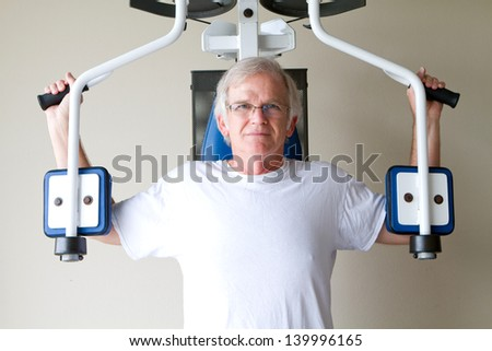 Elderly retired man uses weight training equipment at a gym to improve his health and life. - stock photo