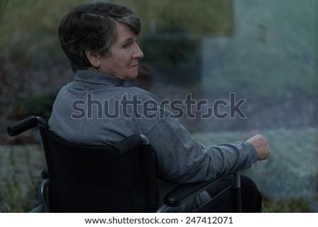 Elderly sad woman looking through the window - stock photo