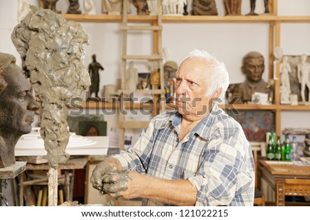 Elderly sculptor making sculpture putting clay on wire skeleton - stock photo