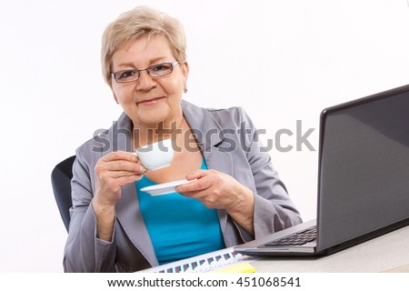 Elderly senior business woman drinking tea or coffee at desk in office, concept of break at work