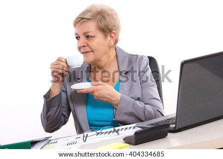 Elderly senior business woman drinking tea or coffee at her desk in office, concept of break at work, analysis of financial chart, business report