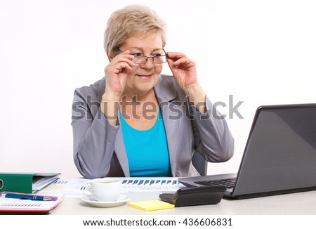 Elderly senior business woman looking at laptop screen and working with financial chart at desk in office, analysis of sales plan, business report - stock photo