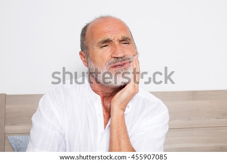 Elderly senior in bed with toothache - stock photo