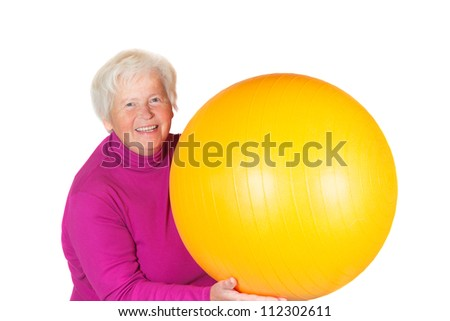 Elderly senior woman holding a yellow pilates or gym ball in her hand with a lovely radiant smile on her face - stock photo