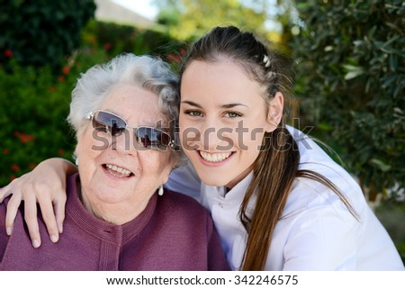 elderly senior woman on wheelchair with nurse outdoor in nursing home hospital garden - stock photo
