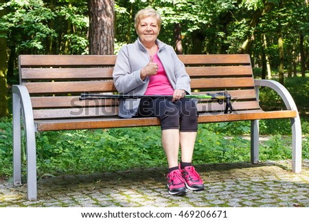Elderly senior woman sitting on bench, resting after nordic walking and showing thumbs up, healthy sporty lifestyles on fresh air in old age