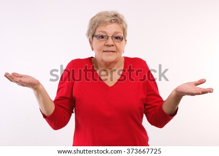 Elderly senior woman throwing up her hands and shrugging shoulders, human emotions and gesture, having no clue - stock photo