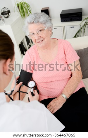 elderly senior woman with a young doctor having medical care at home - stock photo