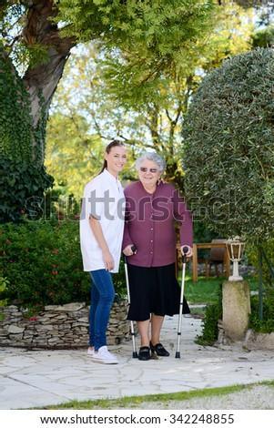 elderly senior woman with nurse walking outdoor in nursing home hospital garden - stock photo