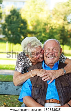 elderly seniors couple in love. man hands over a rose. - stock photo