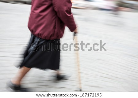 Elderly sick woman with a cane walking down the street. Intentional motion blur - stock photo