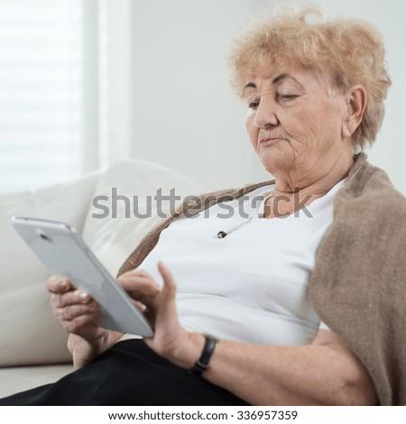 Elderly smart lady using the ipad - stock photo