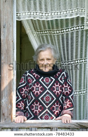 Elderly smile woman is looking out open window of old summer cottage - stock photo