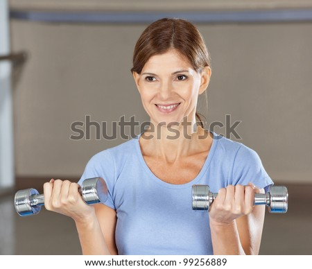Elderly smiling woman doing dumbbell training in gym - stock photo