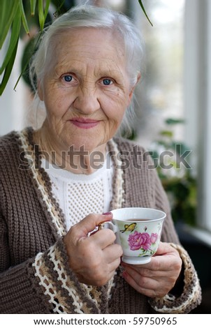 Elderly, smiling woman with cup of tea at the balcony - stock photo
