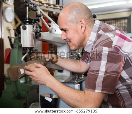Elderly smiling workman sewing leather boots on stitch lathe at factory