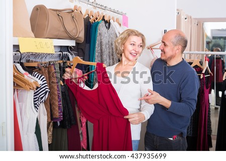 Elderly spanish spouses buying new dress and smiling in boutique - stock photo