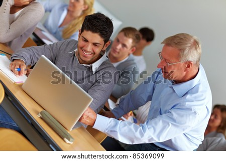 Elderly teacher giving assistance in university class - stock photo