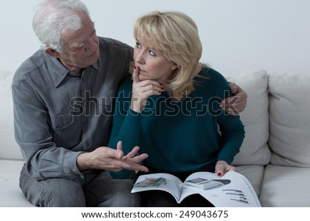 Elderly thoughtful husband cheering up his worried wife - stock photo