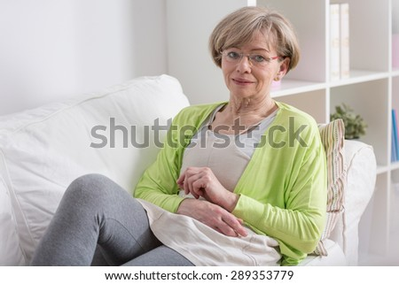 Elderly tired woman resting on couch after work
