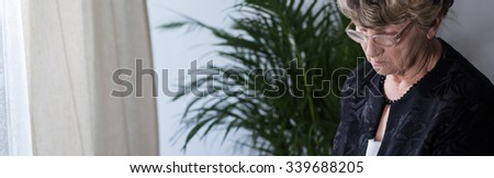 Elderly widow in glasses remembering the past - stock photo