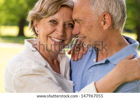 Elderly wife and husband cuddling and smiling outdoors - stock photo