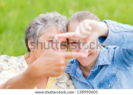 Elderly woman and her daughter framing  their faces - stock photo