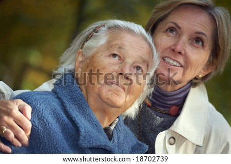 Elderly woman and her middle-aged daughter looking above. Focus on the elderly woman. - stock photo