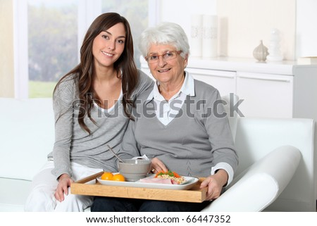 Elderly woman and home carer sitting in sofa with lunch tray - stock photo