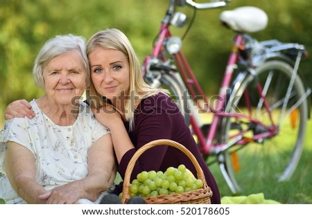 Elderly woman and young woman at the picnic. MANY OTHER PHOTOS WITH THIS SENIOR MODEL IN MY PORTFOLIO.