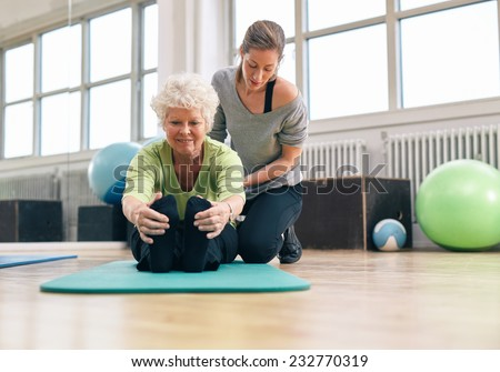 Elderly woman being helped by her instructor in the gym for exercising. Senior woman sitting on fitness mat bending forward and touching her toes with her personal trainer assisting. - stock photo