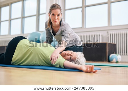 Elderly woman being helped by her personal instructor in the gym for exercising. Female trainer assisting senior woman in her physical training at rehab. - stock photo