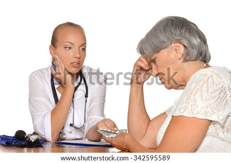 Elderly woman came to young doctor for consultation - stock photo