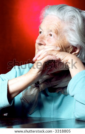 Elderly woman contemplating, portrait on red background - stock photo