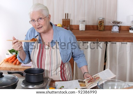 Elderly woman cooking dinner with the help of a recipe - stock photo