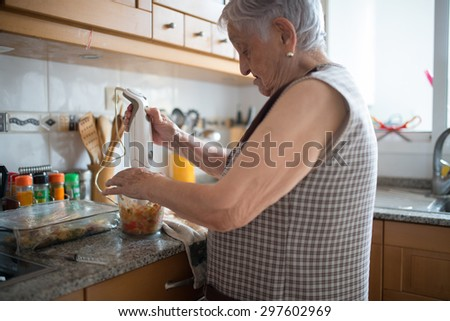 Elderly woman cooking in the kitchen at home - stock photo
